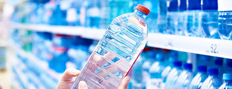 Donna che sceglie bottiglie di plastica